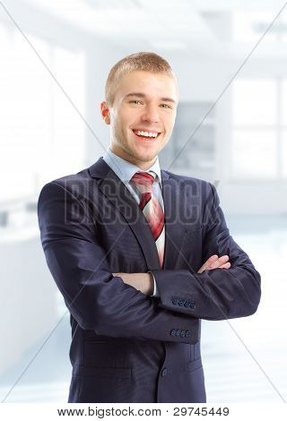 Closeup of a young smiling business man standing in his mordern business office