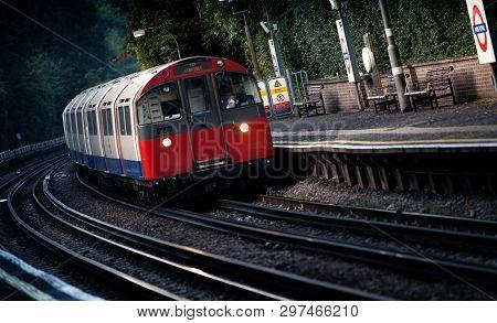 A London Underground Service Heading To Uxbridge Passing Through Park Royal Station, London, Uk - 5t