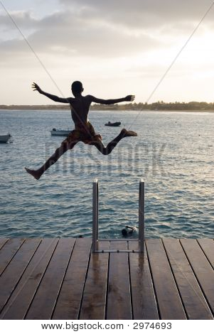 A Boy Jumping Off Pier Into Water.