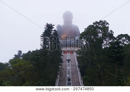Giant Budha Statue In Fog On The Vertex Of Mountain. There Are Stairs To The Budha And Forests Aroun