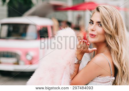 Closeup Portrait Attractive Girl Holding Pink Fur Stole In Hand On Retro Car Background. She Has Lon