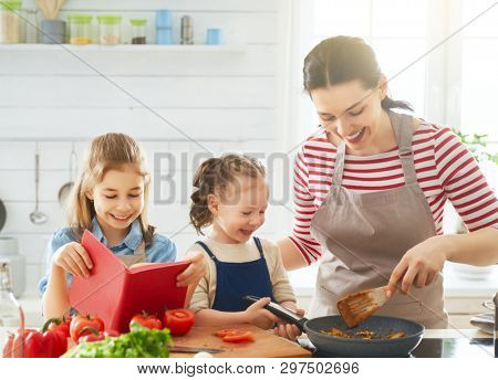 Healthy food at home. Happy family in the kitchen. Mother and children daughters are preparing vegetables.