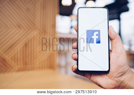 Chiang Mai, Thailand - Mar. 23,2019: Man Holding Xiaomi Mi Mix3 With Facebook App On The Screen. Fac
