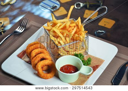 French Fries And Squid Rings In A Basket With Tomato Sauce