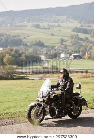 Long-haired Bearded Cool Rider In Sunglasses And Black Leather Clothing Riding Cruiser Powerful Moto