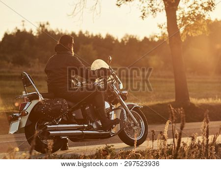 Back View Of Bearded Biker Riding Cruiser Motorcycle Along Empty Narrow Country Road At Sunset On Be