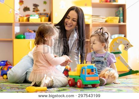 Children Kids Toddlers Playing With Teacher In Kindergarten. Nursery Babies Sitting On Floor Togethe
