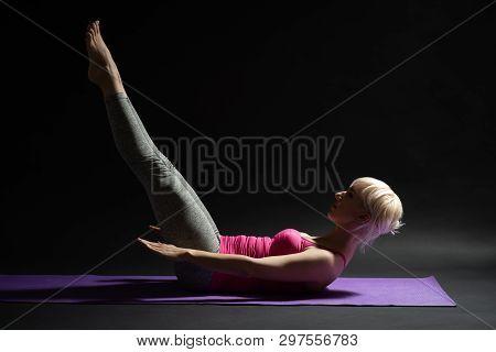 Woman Exercising Pilates. Hundred Exercise. Studio Shot.