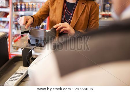 Verkäuferin swiping Kreditkarte im Supermarkt mit Kunden im Vordergrund