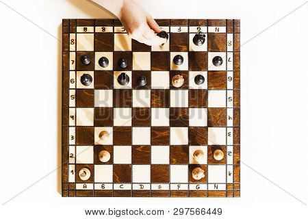 Chess Board On White Background. Little Caucasian Girl Holding A Black Castle In The Hand. Top View.
