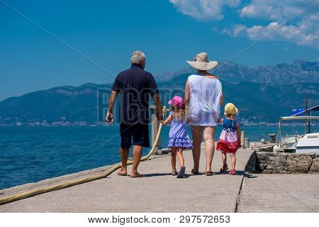 happy grandparents with cute little granddaughters having fun holding their hands while walking  by the sea during Summer vacation  Healthy family holiday concept