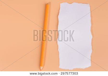 A Piece Of White Torned Paper Over Orange Background With Pencil