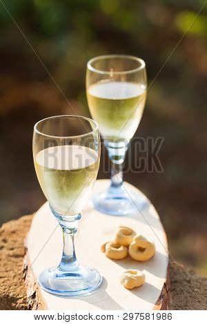 Two Glasses Of Fresh White Wine On A Wooden Board A Traditional Italian Snack - Taralli On A Bright
