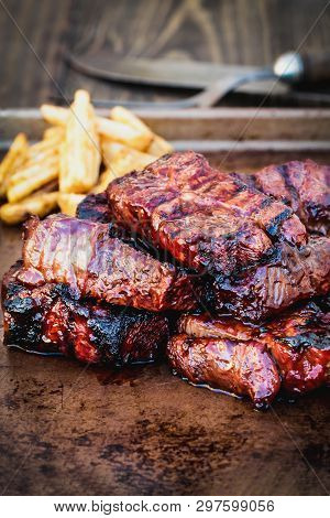 Bbq Boneless Beef Ribs With Barbecue Sauce And Potato Wedges Over A Rustic Background. Extreme Shall