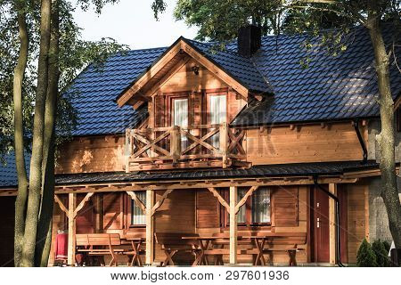 Wooden House In Forests Garden Above The Lake.
