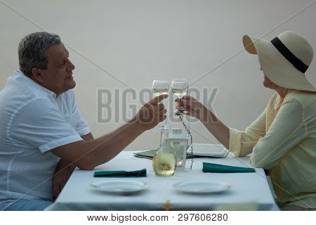 A Middle-aged Couple Sitting At A Laid Table, Clinking Glasses With White Wine And Waiting For Entre