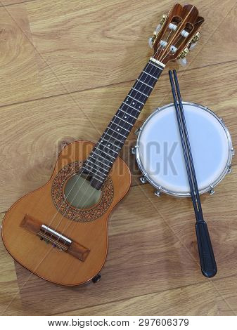 Close-up Of Two Brazilian Musical Instruments: Cavaquinho And Tamborim With Drumstick On A Wooden Su