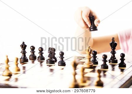 Little Caucasian Girl Holding A Black Castle In The Hand. The Chess Game.