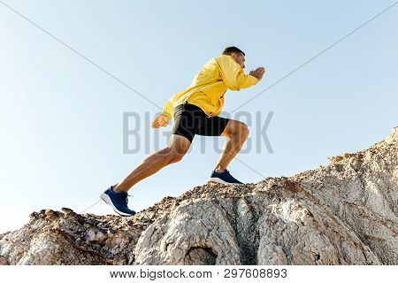 Man Climb Uphill Mountain In Yellow Jacket Background Sky