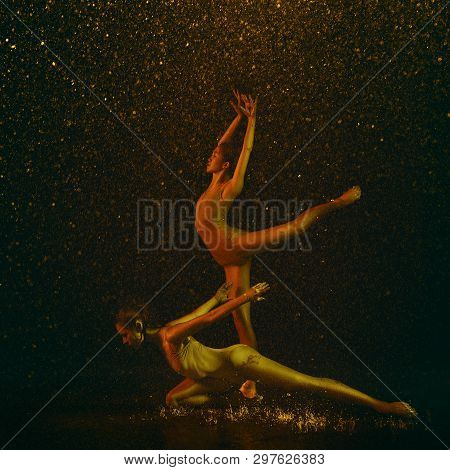 Marvelous. Two Young Female Ballet Dancers Under Water Drops And Spray. Caucasian And Asian Models D