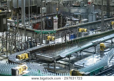 Beer Bottles Moving On Automated Conveyor Line Or Belt. Industrial Brewery And Alcohol Production Eq