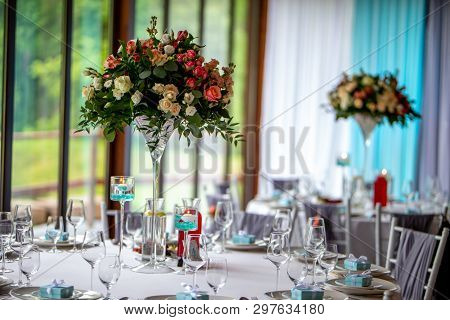 Wedding Table Decoration. Beautiful Bouquet Of Flowers On The Table, Next To Plates,  Glasses And Gi