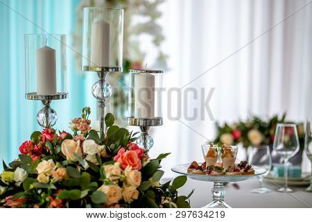 Wedding Table Decoration. Candlestick With Candles, Bouquet Of Flowers And Salads In Plate On The We