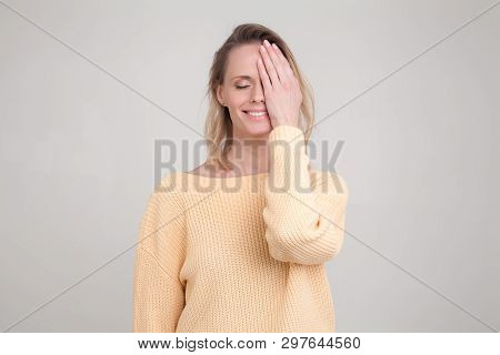 Portrait Of Happy Blonde Woman With Pleased Expression On Her Face, With Eyes Closed, Keeping Her Ha