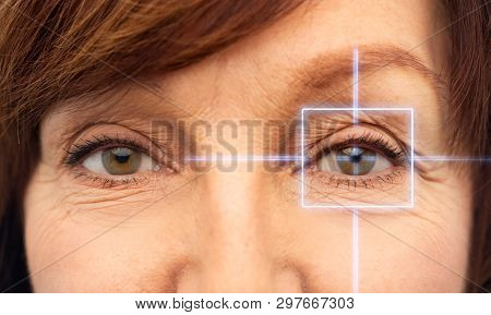 vision, eye surgery and security concept - eyes of senior woman with laser light