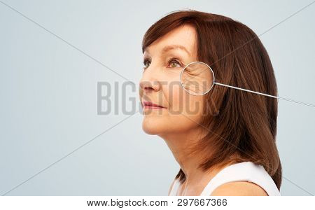 beauty and skin aging concept - portrait of senior woman with zoomed eye wrinkles in pointer over grey background