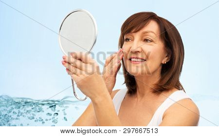 beauty, skin care and moisturizing concept - portrait of smiling senior woman with mirror touching her face over blue background with bubbles in water splash