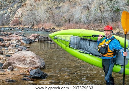 happy senior paddler carrying inflatable whitewater kayak on a shore of mountain river in early spring - Poudre River above Fort Collns, Colorado
