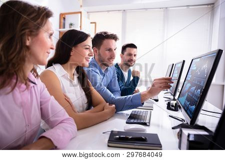 Young Businesspeople Stock Market Broker Analyzing Graph On Computer At Workplace