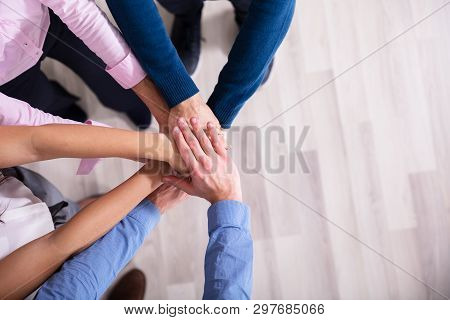 An Elevated View Of Businesspeople Stacking Hands Over Each Other