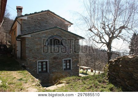 A Structure Of A Particular House. Home In Stone In Nature Where Windows And Doors Seem To Form A Sm