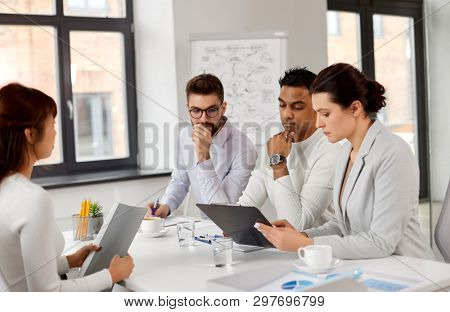 new job, hiring and employment concept - international team of recruiters looking at clipboard and having interview with asian female employee at office