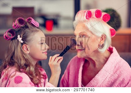 Girl Holding Brush And Putting Facepowder On Face Of Granny