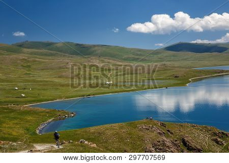 Guy Downhill On A Bike To A Magnificent Mountain Lake. The Sky With Beautiful Clouds Reflected On Th