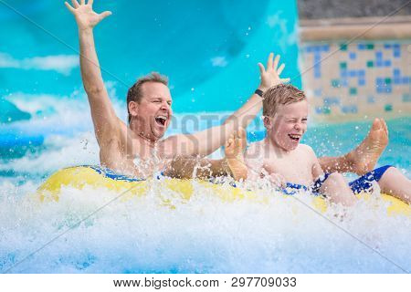 Thrilling expression of a father and his son as they splash down a water slide at an amusement park during a summer vacation. Lifestyle photo showing fun family activities