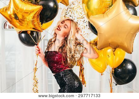 Birthday Party. Blonde Girl In Dressy Outfit Dancing Over White Curtains With Balloons. Pretty Lady