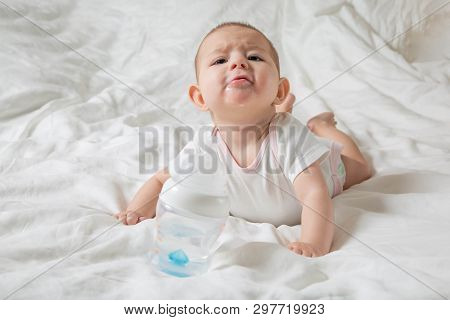 The Baby Is Drooling And Teething. He Lies On A White Bed And Pulls His Hands To A Bottle Of Water.