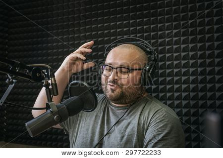 Smiling And Gesturing Radio Host With Headphones On His Head Reading News From Paper Into Studio Mic