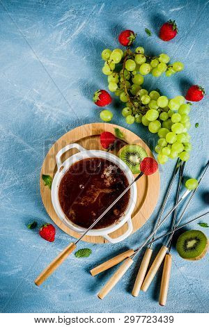 Sweet fruity chocolate fondue dessert with strawberry, grape and kiwi, light blue concrete background copy space poster