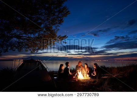 Night Summer Camping On Lake Shore. Group Of Five Young Happy Tourists Sitting In High Grass Around