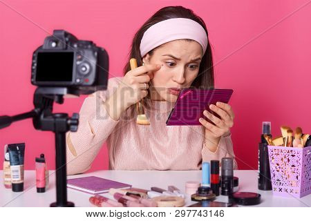 Shot Of Female Blogger Notices Acne Under Her Eyes, Holds Cosmetic Brush And Mirror, Sits At Camera