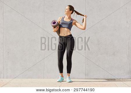 Full length photo of healthy young woman in sportswear holding yoga mat, touches her ponytail, be photographed after training, model posing solated over gray background. Copy space for advertisment. poster