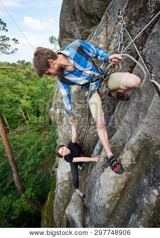 Happy Woman And Man Climbing On Rock. Carefree Hiker Smiling Her Friend And Hanging On Rope. Man Hel