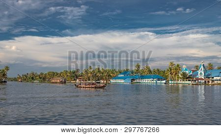 Blue Church On The Edge Of Alleppey Backwater With Houseboats Trail And Palm Tree Giving The Real Fe