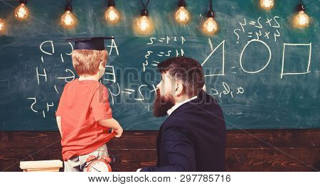 Individual Education Concept. Teacher And Child Turned Back In The Classroom. Boy Listening To The E