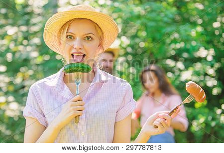 Girl Holds Forks With Sausage And Cucumber. Alternative Nutrition For Vegetarians. Choice Meat Or Ve